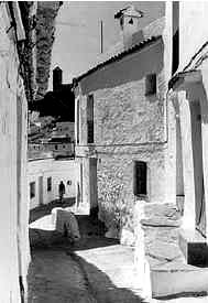 Figure 6: A street in Casares, Andalucia region, Spain. Note the steps to the front doors of the houses on the right are within the fina space of the houses. Photo courtesy: www.justcasares.com