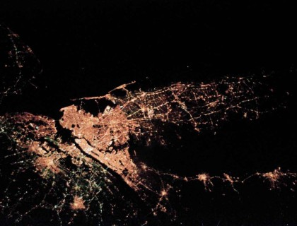 Recent research at SFI considers the city not only as people and infrastructure, but as a network of interactions in space and time. In this nighttime satellite image, populated areas branch out from the New York City metropolitan area. (NASA)
